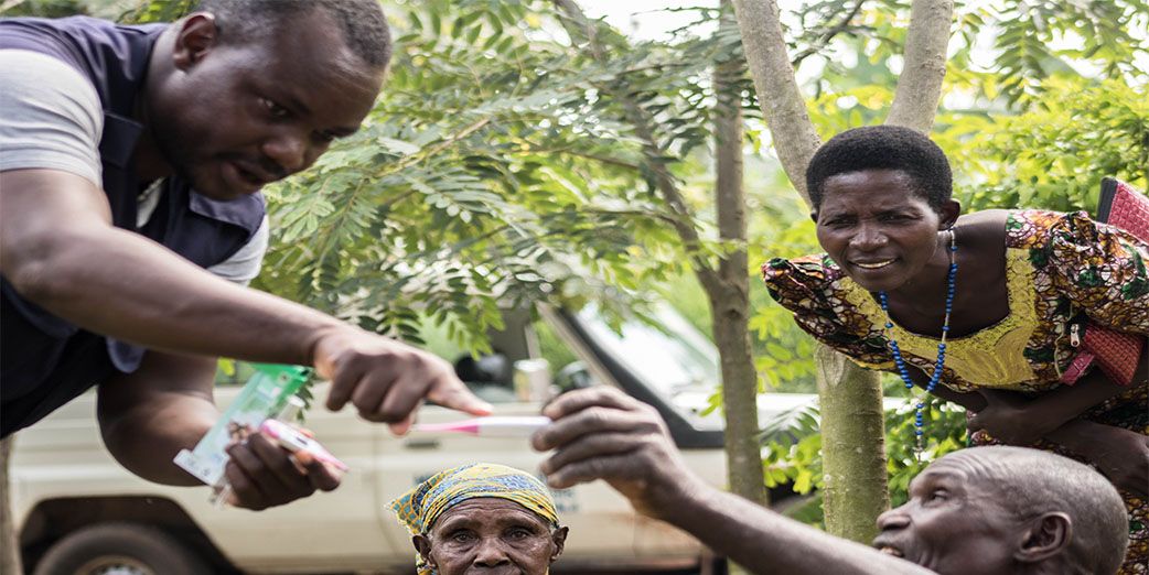 A community Member being shown how to use a thermometer during the Ebola Outbreak In Kasese District, Uganda.