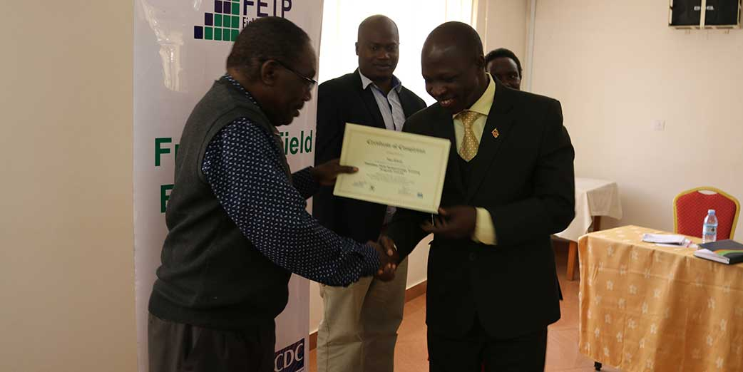Frontline Cohort VIII graduation participant, Dr Yayi Fred - District Health Officer, receives his certificate during the graduation